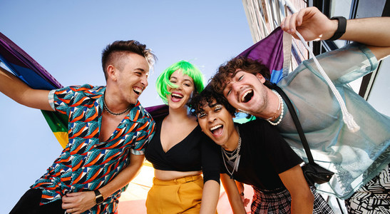 Four young people celebrating their queer identities together