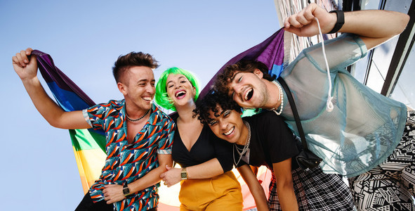 Group of LGBTQ people celebrating with pride flag