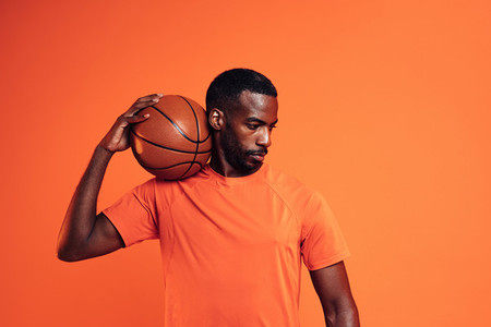 Male athlete standing in the studio with basket ball on his shoulder looking down