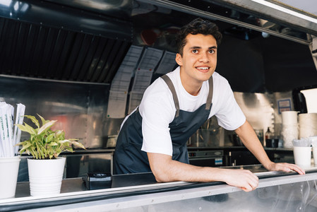 Portrait of smiling male owner wearing apron standing in food truck