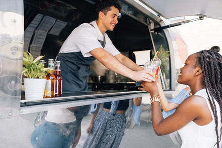 Side view of women buying drinks from a male owner at a food truck