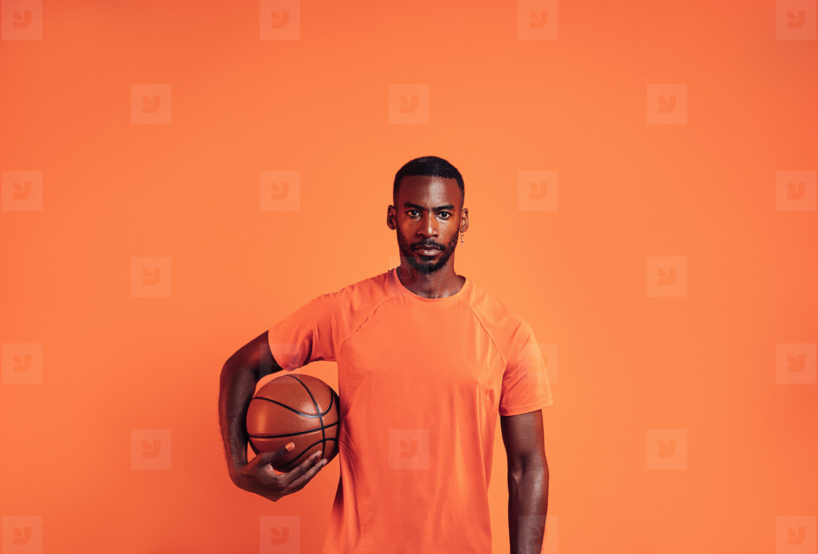 Portrait of a confident young man holding a basket ball against an orange background