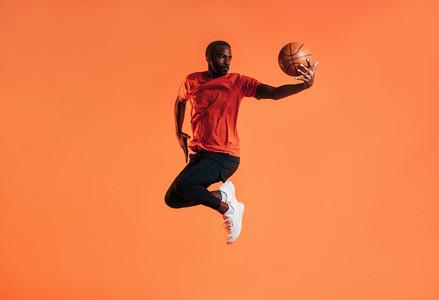 Young man in sportswear practicing basketball against an orange background  African male athlete jumping in the air with basket ball in studio