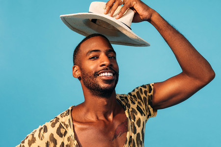 Portrait of a cheerful young man holding hat over his head against a blue background