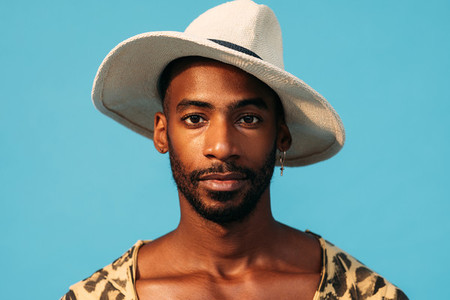 Close up portrait of a handsome man in hat against a blue background
