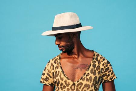 Portrait of a stylish man in hat posing against blue background looking sideways