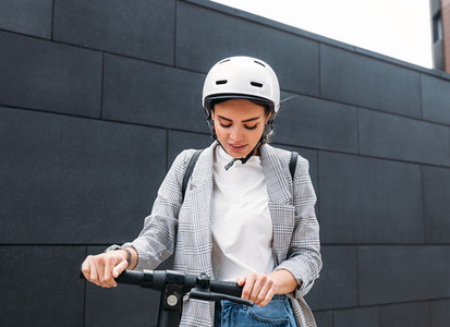 Young caucasian woman wearing white cycling helmet holding handlebar of electric scooter