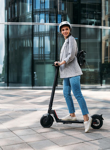 Stylish cheerful woman standing on electric push scooter and looking away