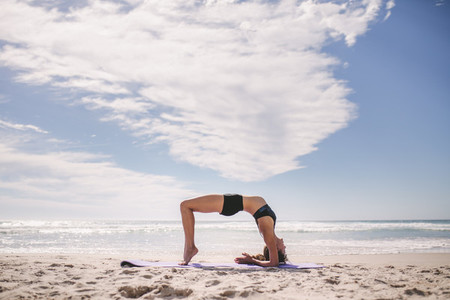 Sporty woman doing back bend at the beach
