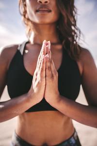 Fitness woman meditating outdoors