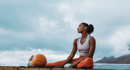 Fitness woman relaxing after workout on rooftop