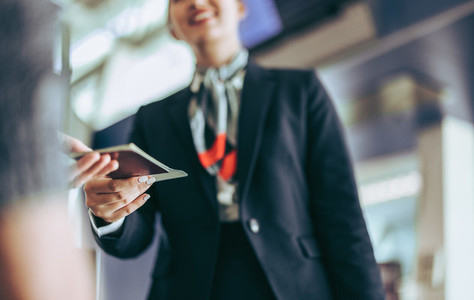Flight attendant checking passport