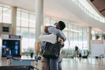 Wife giving good bye hug to her husband at airport