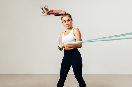 Young Asian athlete exercising with a resistance band against white background  looking away