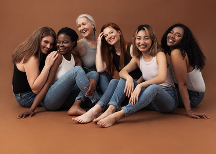 Six women of different ages sitting together in studio on brown background  Multi ethnic group of diverse females having good times