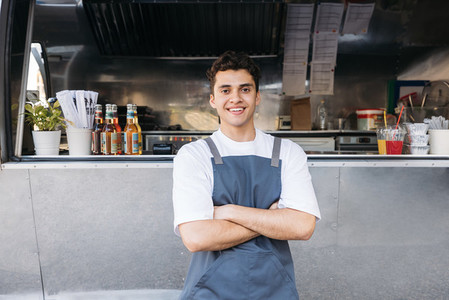 Portrait of a confident entrepreneur  Food truck owner wearing apron standing with crossed arms