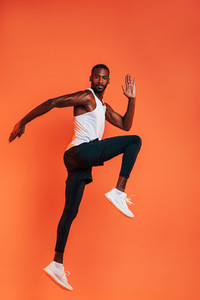 Sportsman doing a stretching workout  Full length of healthy fitness man exercising against an orange background