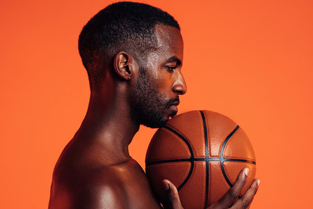 Side view of sportsman with basket ball under his chin against orange background in studio