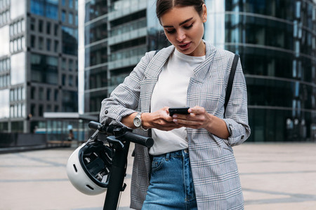 Young woman in stylish clothes holding smartphone while standing in front of an office building