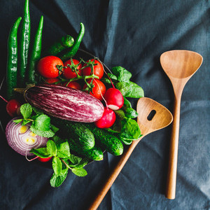 Various fresh colorful vegetables in a plate on a table with wooden kitchen utensils  Top view