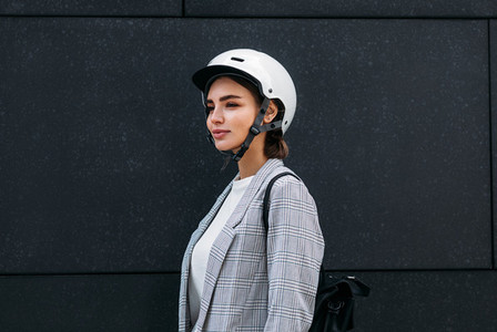 Businesswoman in white cycling helmet wearing backpack standing against a black wall outdoors