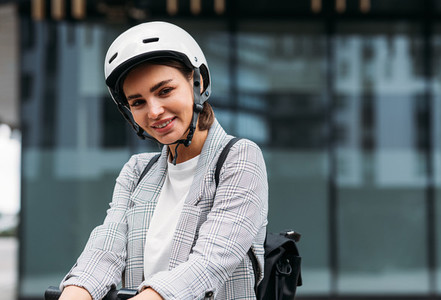 Beautiful smiling businesswoman in cycling helmet lean on handlebar of electric scooter looking at camera