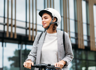 Beautiful woman in white cycling helmet holding a handlebar of electric scooter looking away