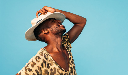 Happy stylish man hiding his face with white straw hat against blue background