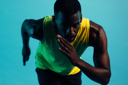 Close up of male athlete in sports clothes preparing to run standing against a blue background
