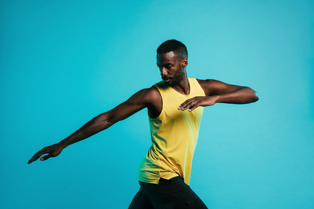 Sportsman doing stretching exercises in studio over blue background