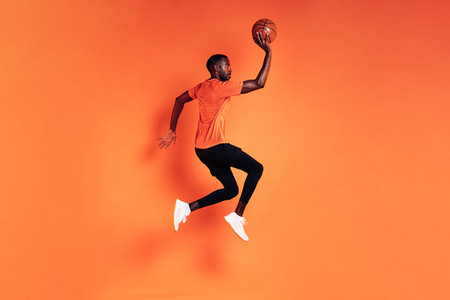 Male athlete jumping with basket ball  Side view of sportsman exercising over orange background