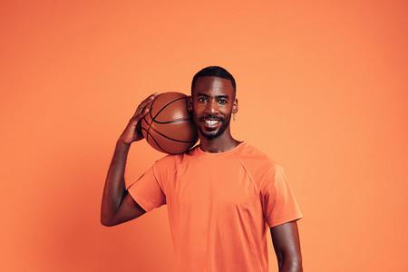 Smiling sportsman with basket ball on his shoulder posing over orange background in studio