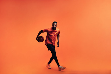 Full length of young male athlete dribbling basket ball in studio
