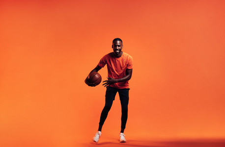 Young smiling man dribbling a basket ball over an orange background in studio