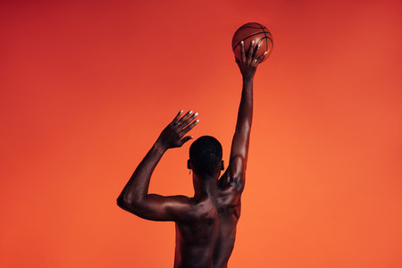 Back view of unrecognizable African American male athlete throwing basket ball against an orange background