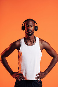 African American male athlete listening music through wireless headphones  Man in sportsclothes relaxing during fitness training