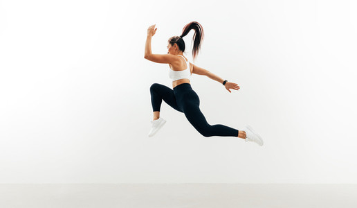 Female athlete running and jumping against white backgroung