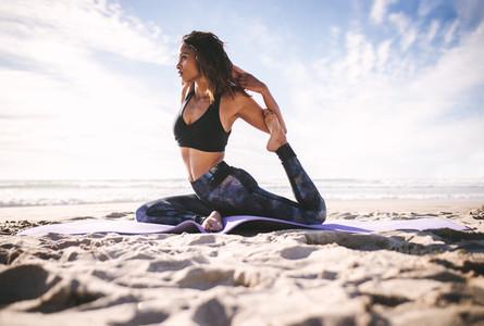 Young girl doing king pigeon yoga pose on the beach