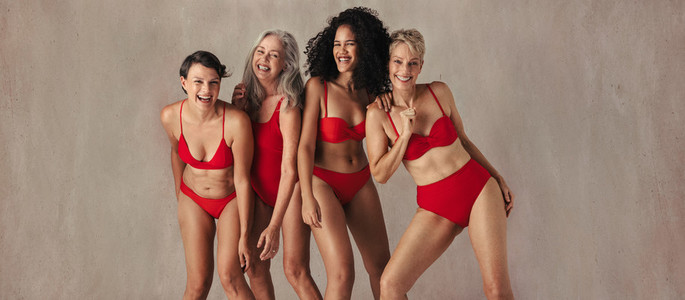 Four women of all ages having fun in red swimwear