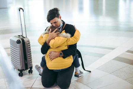 Mother hugging and kissing her child at airport
