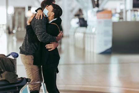 Woman receiving man at airport arrival after pandemic