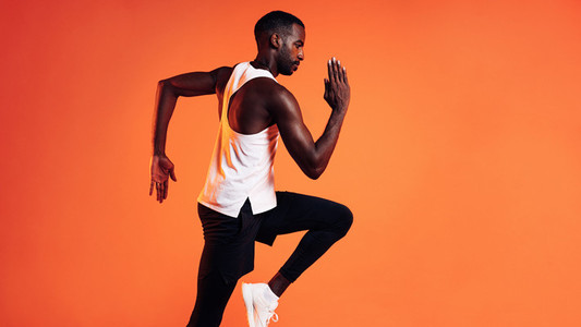 Side view of a male runner sprinting over orange background