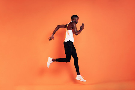 Male athlete wearing sports clothes running against an orange background