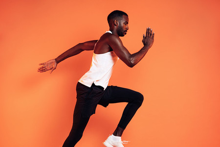 Cropped shot of a male runner sprinting in studio over orange background