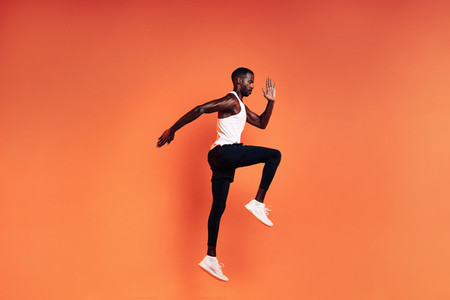 Fit man jumping in studio  Male runnner warming up before workout against orange background