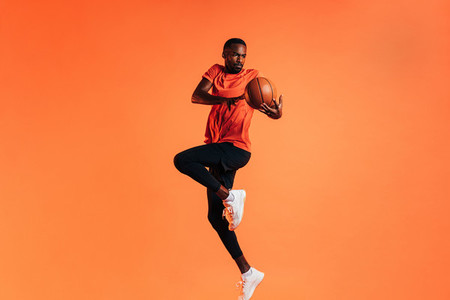 Sportsman jumping in studio against an orange background with basket ball