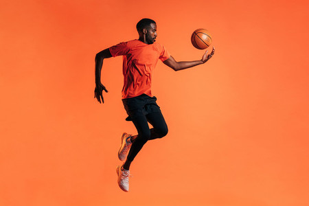 Side view of young male jumping and throwing up a basket ball in studio