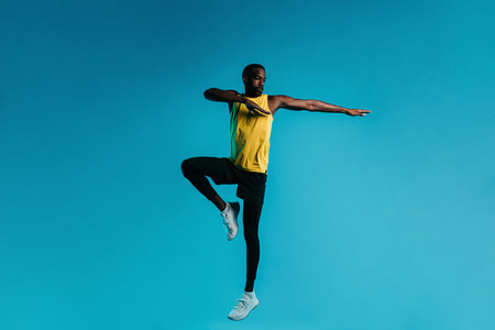 Young man in sportswear jumping and stretching his arms over blue background
