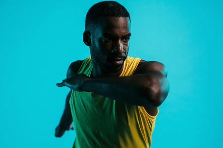 Close up of male athlete stretching arms and body in studio over blue background
