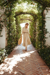 Graceful young woman walking alone a plant tunnel
